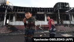 Подростки на фоне сожженного здания в селе Масанчи. Жамбылская область, 8 февраля 2020 года.