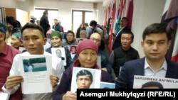 Казахи родом из Синьцзяна с фотографиями родственников, которые, по их словам, находятся в «лагерях политического перевоспитания» в Китае. Нур-Султан, 27 ноября 2019 года.